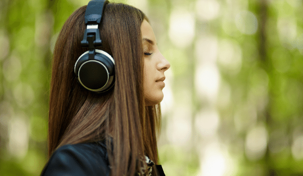 girl with brunette hair listening to music outside
