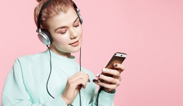 blonde girl with hair in a bun listening to music
