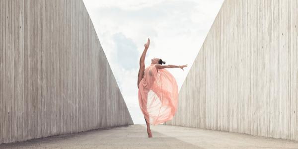 Lyrical dancer in flowy costume dancing on walkway