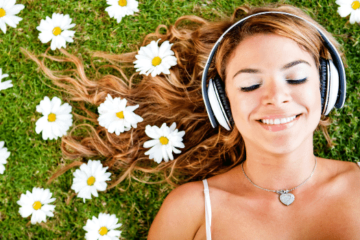 Girl laying in grass with flowers in her hair listening to music
