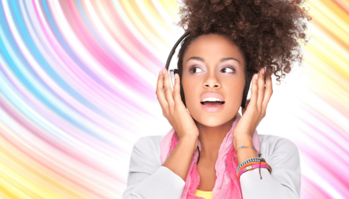 young woman listening to music on headphones on colorful background