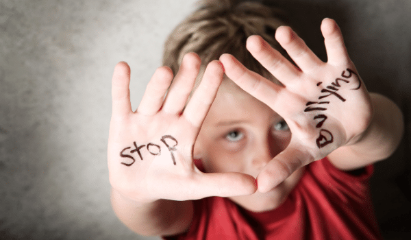 Boy with stop bullying written on his hands