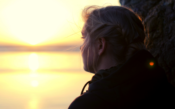 blonde girl looking out over water and thinking about her imperfect relationship and its challenges