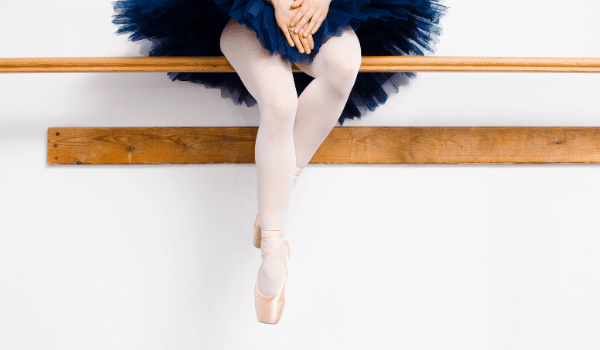 Dancer sitting on ballet barre